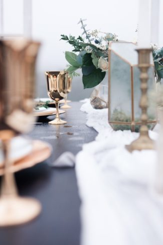focussed on gold goblets at end of table