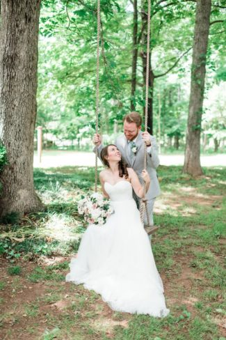 groom behind bride on a tree swing