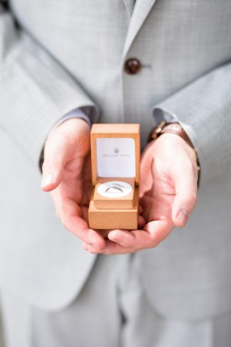 groom holding wood ring box