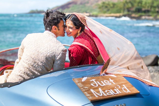 newlyweds drive classic car on Maui coast