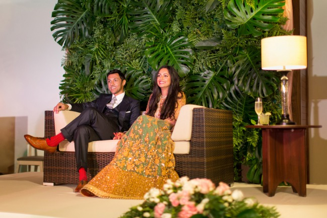 newlyweds sitting on rattan couch