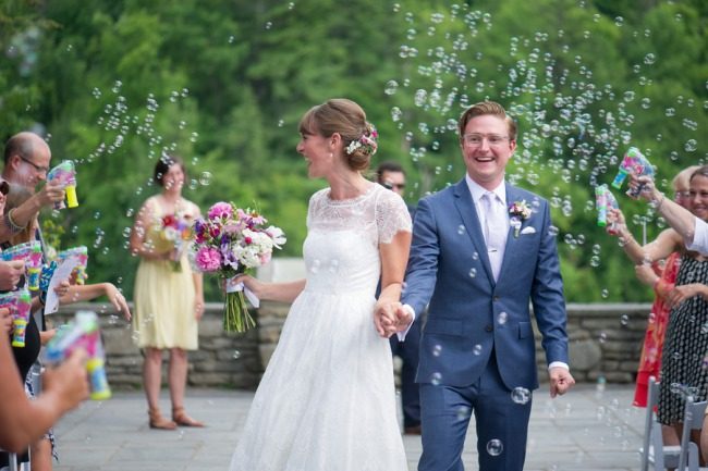 newlyweds walk down aisle with bubbles
