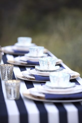 teacups on plates and striped tablecloth