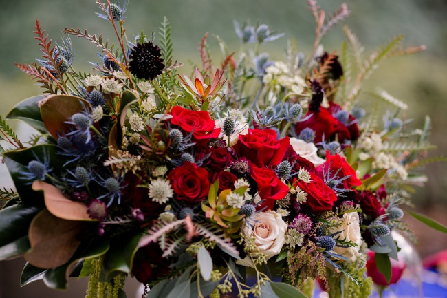 bridal bouquet with blue thistle and red roses