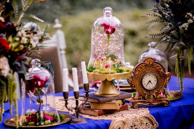 clock, glass case rose, books on table