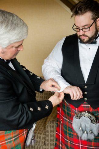 groom putting on cufflinks