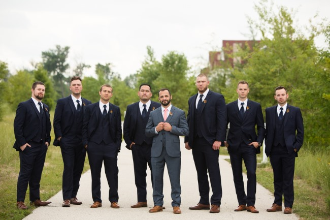 groomsmen wearing suits stand in a row