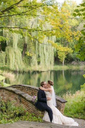 newlyweds sit on bridge with water in back
