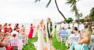 newlyweds walk on grass aisle in Maui