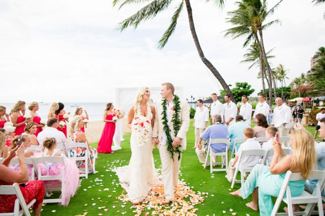 newlyweds walk on grass aisle in Maui