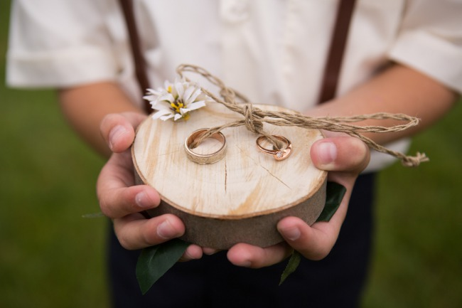 ring bearer holding wood round with rings on it
