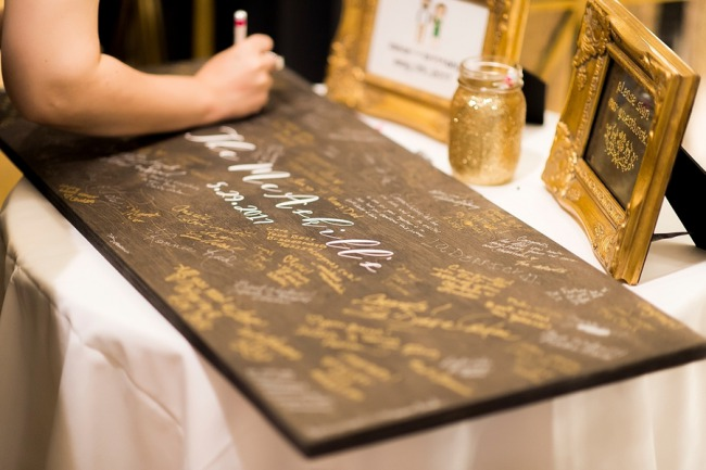 signing guest book board in gold pen