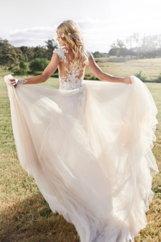 styled bride holds out dress
