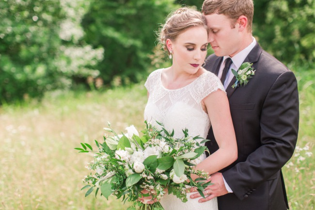 styled couple in field with bouquet