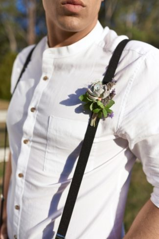 styled groom with suspenders