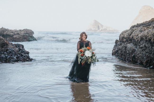 black dressed bride in surf