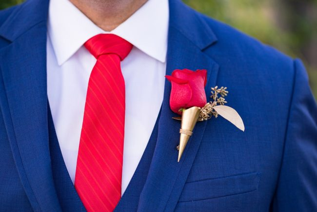 blue suit with red tie and boutonniere