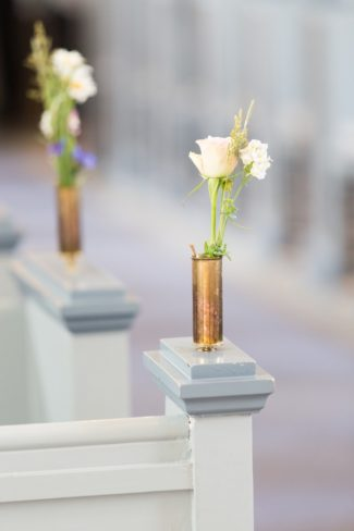brass holders with flower at church ceremony