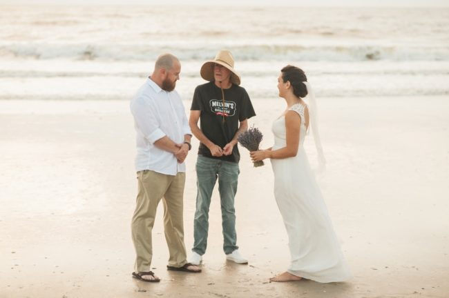 bride and groom with officiant on beach