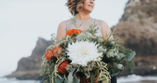 bride holds large bouquet on beach