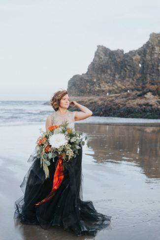 bride in black wading in water