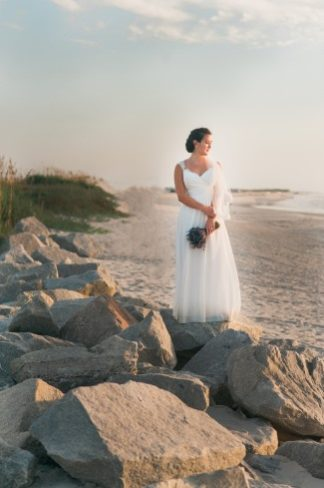 bride on rocks with bouquet
