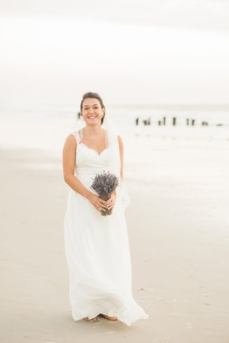 bride with lavender bouquet on Carolina Beach sand