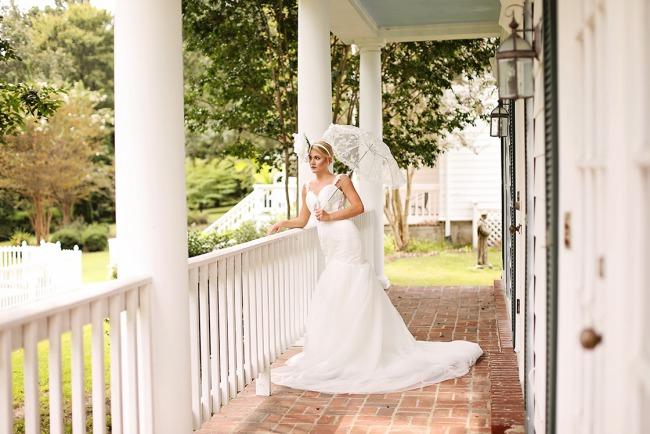 bride with parasol leans over porch railing