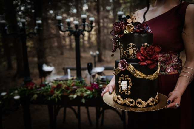 holding black and gold wedding cake