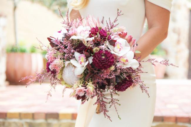 holding violet floral bouquet