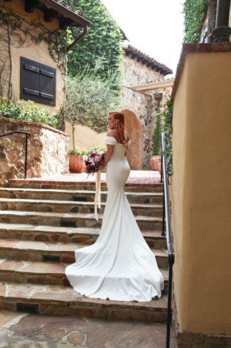 model in white wedding dress on steps