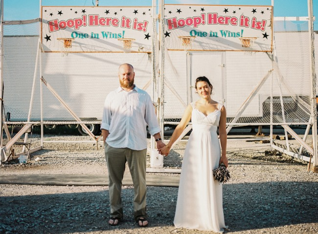 newlyweds stand in front of basketball carnival game