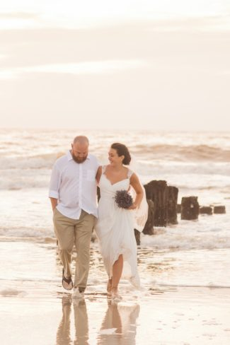newlyweds walk on shoreline