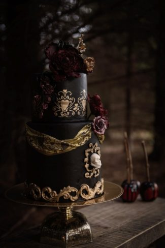 ornate black wedding cake with gold