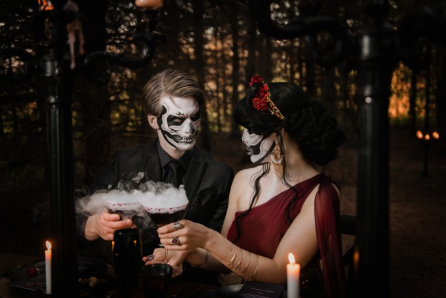 skeleton makeup couple toast with smoking martinis