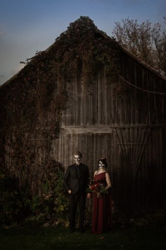 styled Halloween couple in front of barn