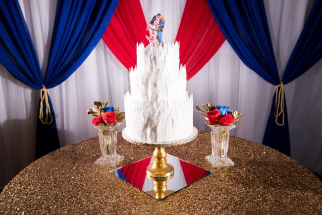 styled white cake for superman and wonder woman