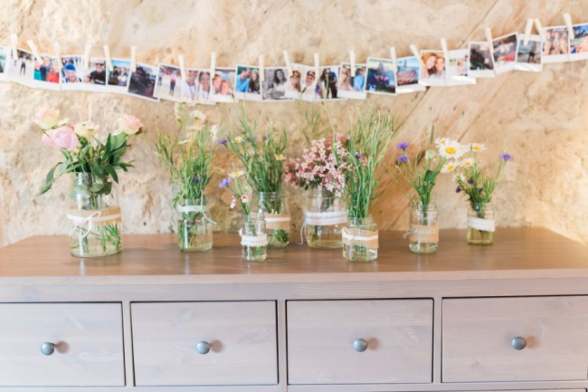 table with grass in jars and photos above