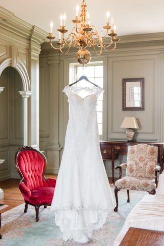 wedding gown hangs from chandelier