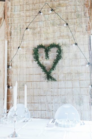 white wall with heart wreath and lights
