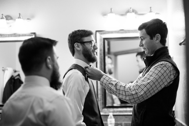 black and white of groom getting ready