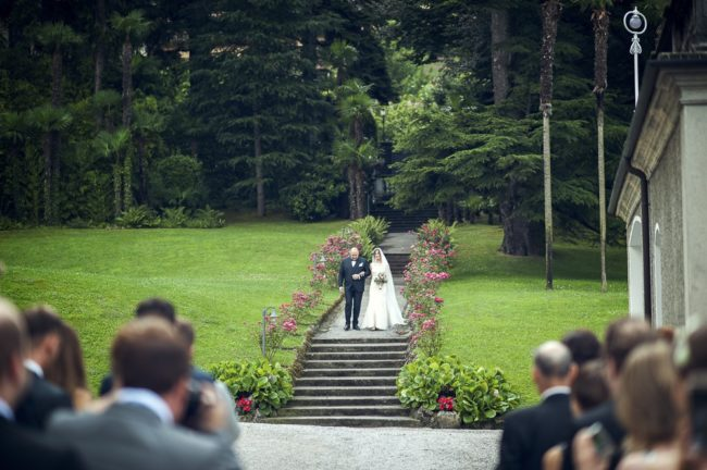 bride and father walk down path
