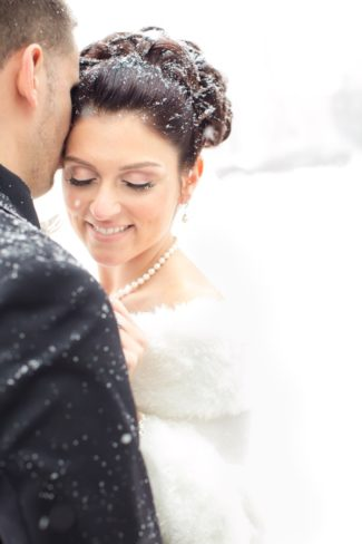 bride showing off pearl necklace and eyelashes