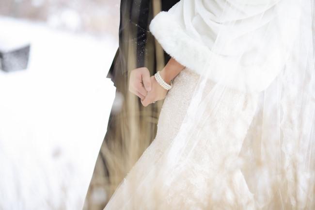 bride wearing pearl bracelet in snow