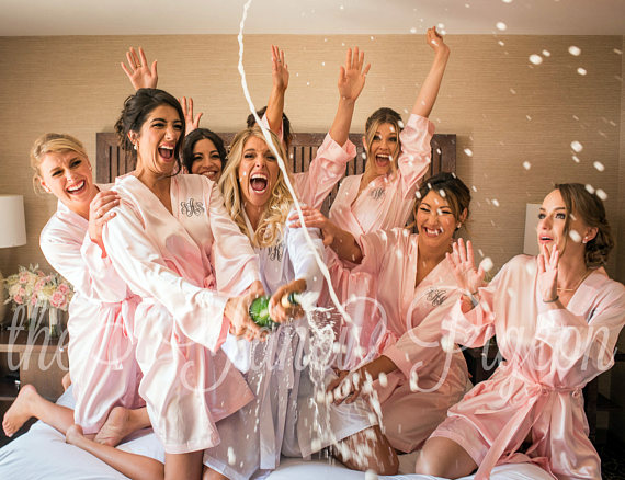 bridesmaids in robes pop champagne