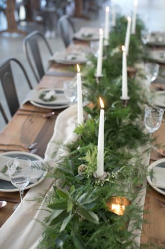 candles burn among greenery on table