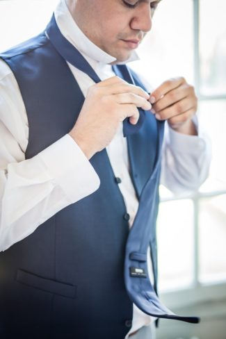 groom putting on necktie
