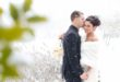 groom with bride in white shawl as snow falls