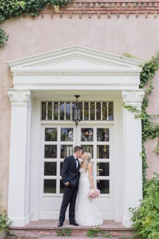 newlyweds kiss out front of los Poblanos Estate