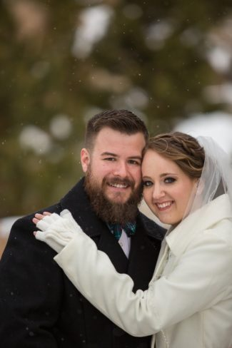 newlyweds smiling as snow falls
